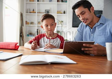 Hispanic pre-teen boy sitting at table working with his home school tutor, using tablet computer