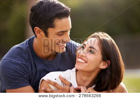 Young Hispanic couple looking at each other smiling, close up