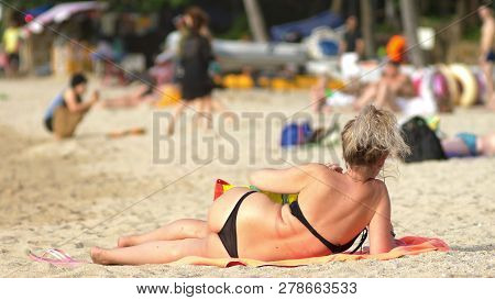Close Up. Unrecognizable People Resting On The Beach, With A Lot Of Unrecognizable People Sunbathing