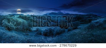 Beautiful Countryside Panorama In Springtime At Night In Full Moon Light. Grassy Hills And Meadows.