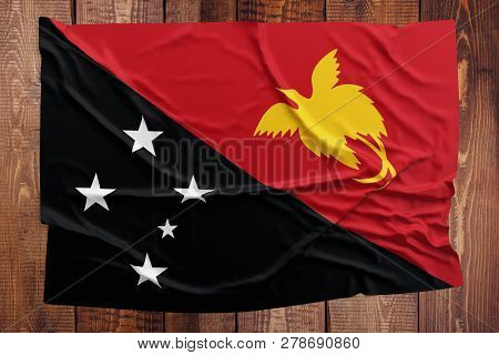 Flag Of Papua New Guinea On A Wooden Table Background. Wrinkled New Guinean Flag Top View.