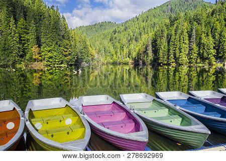 Colorful Boats Docked On A Mountain Lake, Green Forest Mirroring In Lake. Natural Dam Lake In Forest