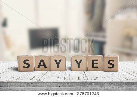 Say Yes Sign On A Wooden Desk In A Bright Room With A Blurry Background