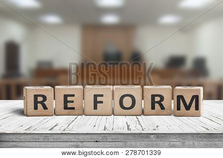 Reform Sign On A Desk With A Blurry Background Of A Court Room