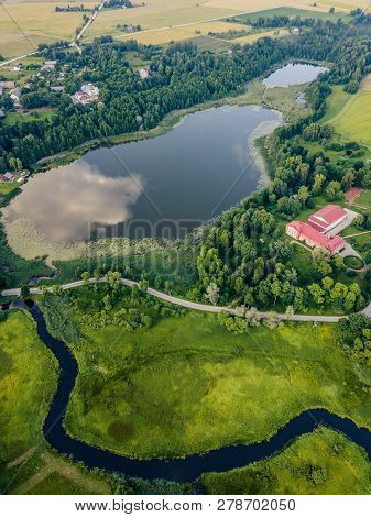Aerial Photo Of Countryside Village Between Trees And With Big Blue Lake Besides It In Early Spring