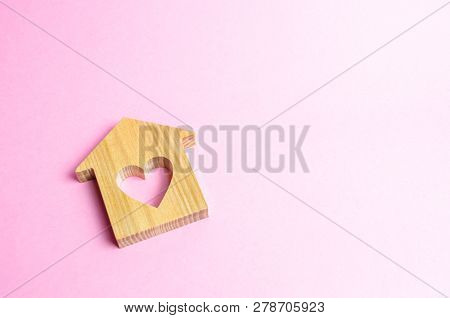 House With A Heart On A Pink Background. The Concept Of Finding A Rental House Or Apartment For A Ro