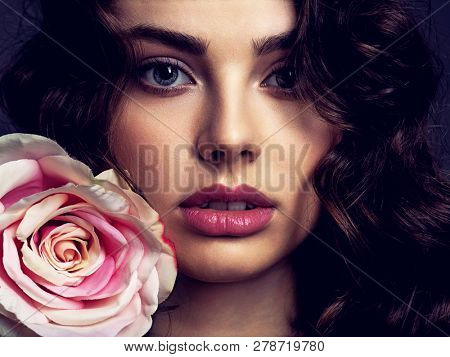 Beautiful face of a young woman with a smoky eye makeup  and rose flower. Sexy woman with long curly hair. Portrait of an attractive female posing at studio. Art. Fashion model