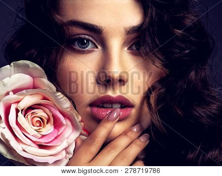 Beautiful face of a young woman with a smoky eye makeup  and rose flower. Sexy  brown-haired woman with long curly hair. Portrait of an attractive female posing at studio. Art. Fashion model.