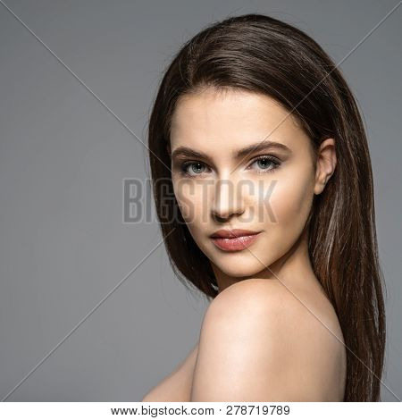 Portrait of beautiful young brunette woman with clean face. Beautiful face of young adult woman with clean fresh skin - isolate