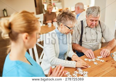 Senior couple playing puzzle in the nursing home cared for by a geriatric nurse