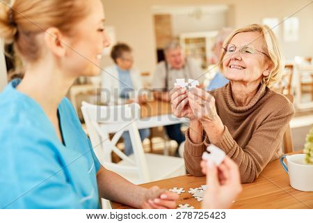 Senior woman with dementia or Alzheimer playing puzzle with a nursing assistant