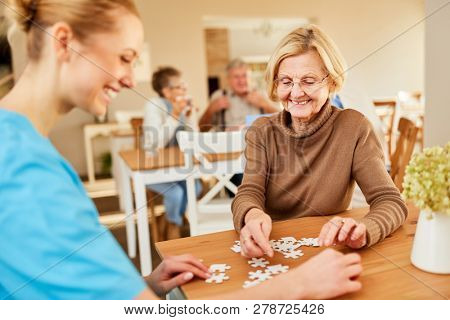 Senior woman and nursing have fun playing puzzle together in retirement home