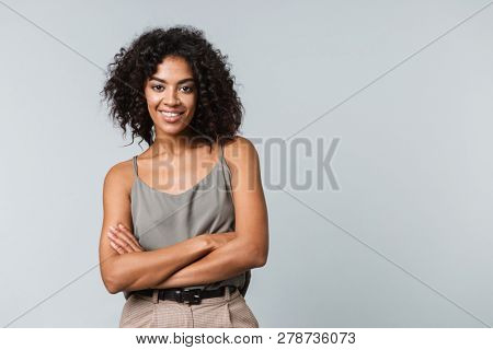 Happy young african woman casually dressed standing isolated over gray background, arms folded