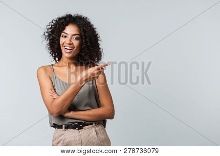 Happy young african woman casually dressed standing isolated over gray background, pointing away