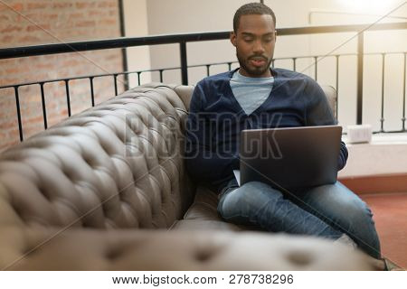 Relaxed black man sitting on sofa working on computer in modern office
