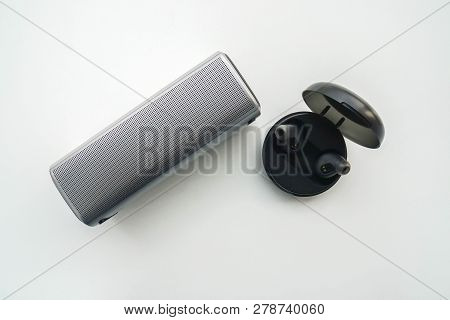 Isolated Top View Of Portable Speaker And Wireless Earphone In Trendy Case For Battery Charging