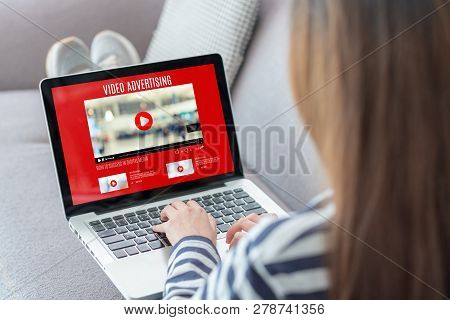 Shoulder View Of Woman Watching Video Online With Advertising On Laptop Computer On Sofa At Home.vir
