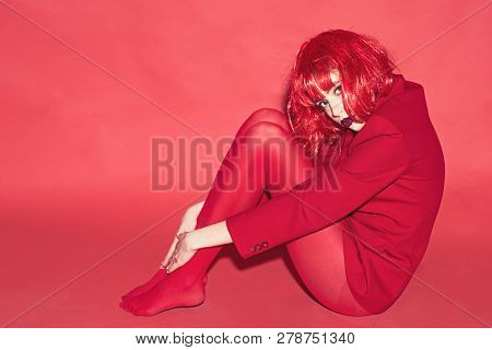 Fashion Concept. Lady Looking At Camera And Sits On Floor. Woman With Makeup And Red Wig Posing In T