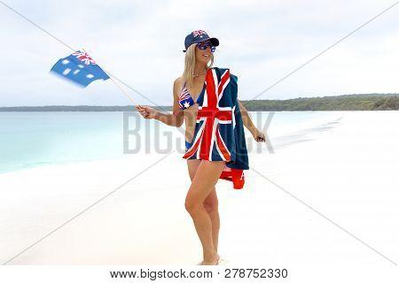 Aussie Girl Waving An Australian Flag On Beautifulo Pristine Beach. She Is Also Has Flag Printed Hat