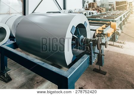 Worksop with machinery tools and equipment, rolls of galvanized steel for production metal pipes and tubes in factory, toned poster