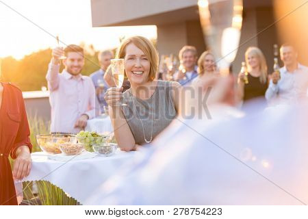 Many people saying cheers and showing their champagne glasses full of sparkling wine to each other whilst enjoying an outdoor party on a roof top restaurant at sunset
