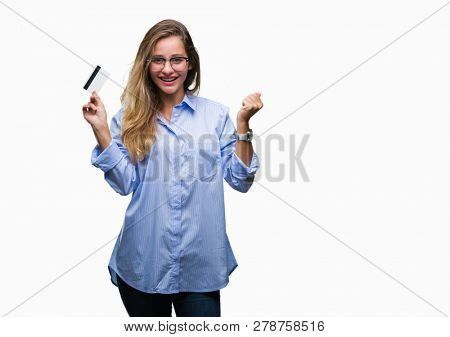 Young beautiful blonde woman holding credit card over isolated background screaming proud and celebrating victory and success very excited, cheering emotion
