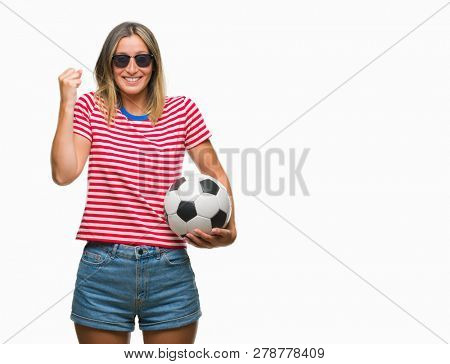 Young beautiful woman holding soccer football ball over isolated background screaming proud and celebrating victory and success very excited, cheering emotion
