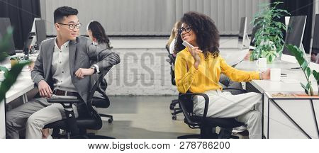 Multiracial Young Business People Smiling Each Other While Working Together In Open Space Office