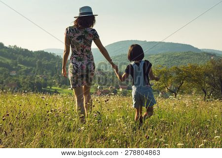 Mother And Child In Summer Vacation. Mother And Child Walking In Meadow In Vacation. Summer Vacation