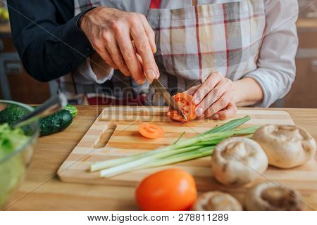 Cut View Of Man And Woman Hands Holding Knife And Cutting Tomato At Table. He Help Her. There Are Gr
