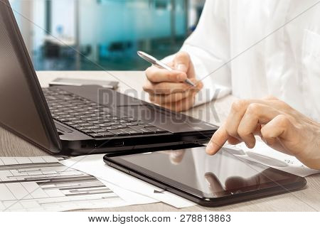 Close Up Of Businessmans Hand Analyzing Graph On Digital Tablet. Time Is Money Concept.