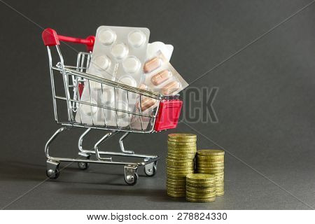 Medicines, Pills, Drugs On  Background Of Metal Coins In  Grocery Cart. Concept Of Increasing The Pr