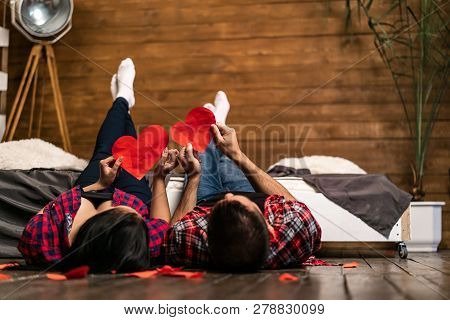 Romantic Couple Lying On Wooden Floor Near The Bed And Holding Red Hearts Shape At Home. True Feelin