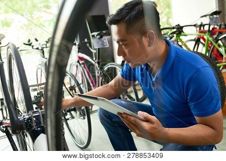 Bicycles Shop Owner With Digital Tablet Checking Every Item In Store