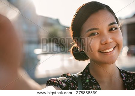 Smiling Young Asian College Student Standing Outside Taking A Selfie