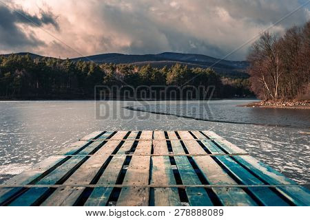 Mole (pier) On The Lake. Wooden Bridge In Forest In Winter Time With Blue Frozen Lake. Lake For Fish