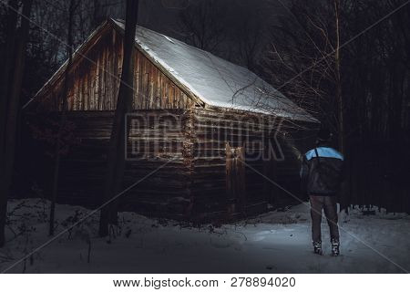 Man (photographer) Standing In Front Of The Abadoned And Creepy Cottage In Forest In Winter. Man On