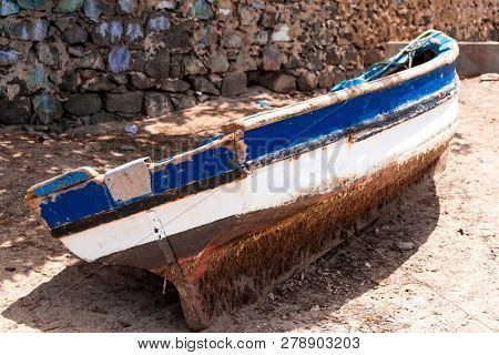 Old fishing boat on the shore. Boat with nets waiting for fishermen on the beach of Cape Verde