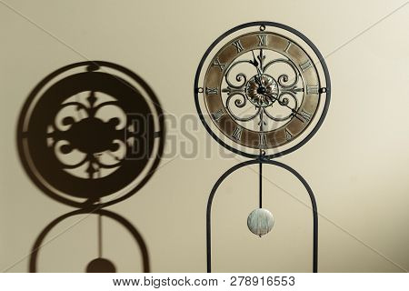 Old Antique Clock Representing Time With Shadow On Wall