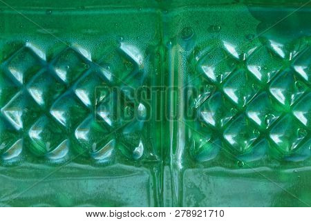 Plastic Green Texture With A Pattern And Drops Of Water On The Bottle
