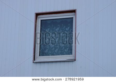 Small Square Window On The Gray Wall Of The Building