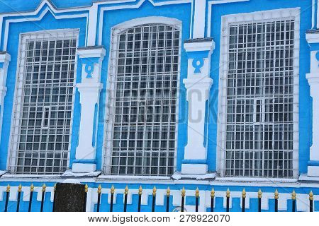 Three Large Old Windows With Iron Bars On The Blue White Wall Of The Building Behind The Black Fence