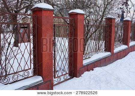 Part Of A Red Fence With A Door Of Iron Rods And Concrete Under White Snow
