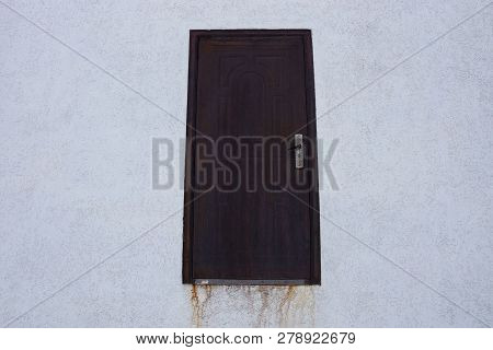 Brown Metal Closed Door On A Gray Concrete Wall Of A Building