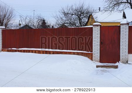 Part Of A Long Red Metal Fence And A Closed Door In White Snow Outside