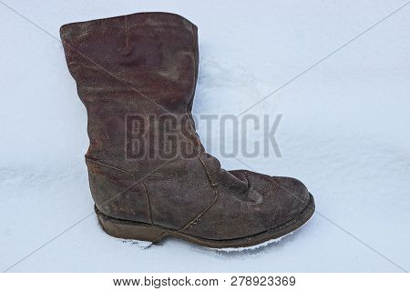 An Old And Dirty Brown Leather Boot Stands In A Snowdrift Of White Snow