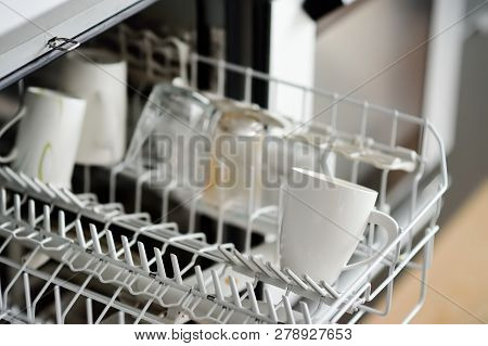 Open Dishwasher With Dirty Crockery In The Modern Kitchen. Close-up. Domestic Appliances For Help An