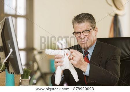 Angry Professional Man Jabbing A Voodoo Doll