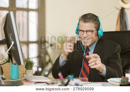 Handsome Creative Business Man Listening To Headphones And Being Silly