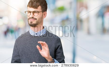 Young handsome smart man wearing glasses over isolated background disgusted expression, displeased and fearful doing disgust face because aversion reaction. With hands raised. Annoying concept.